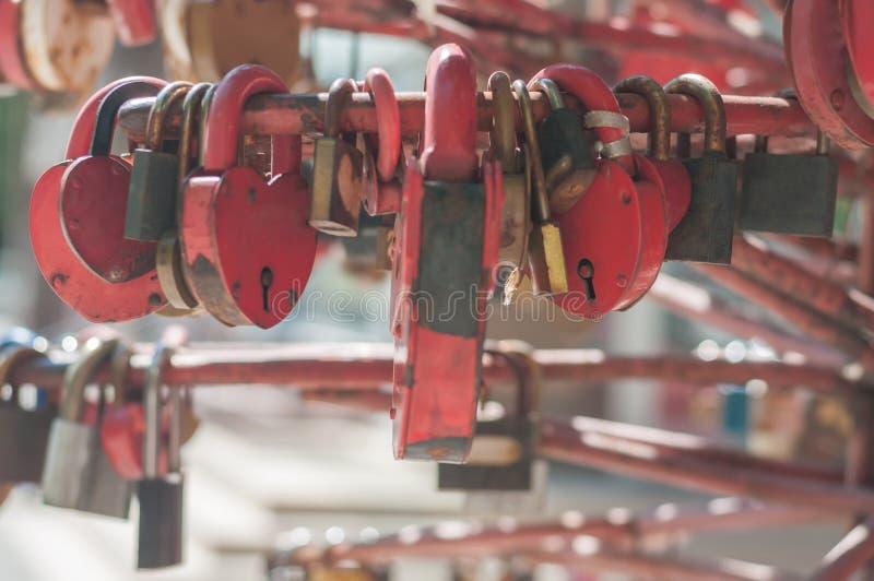 Viele roten gealterten Metallverschlüsse in Form eines Herzens auf dem Ralling an einem sonnigen Tag, Nahaufnahme, weiches Licht, stockbild