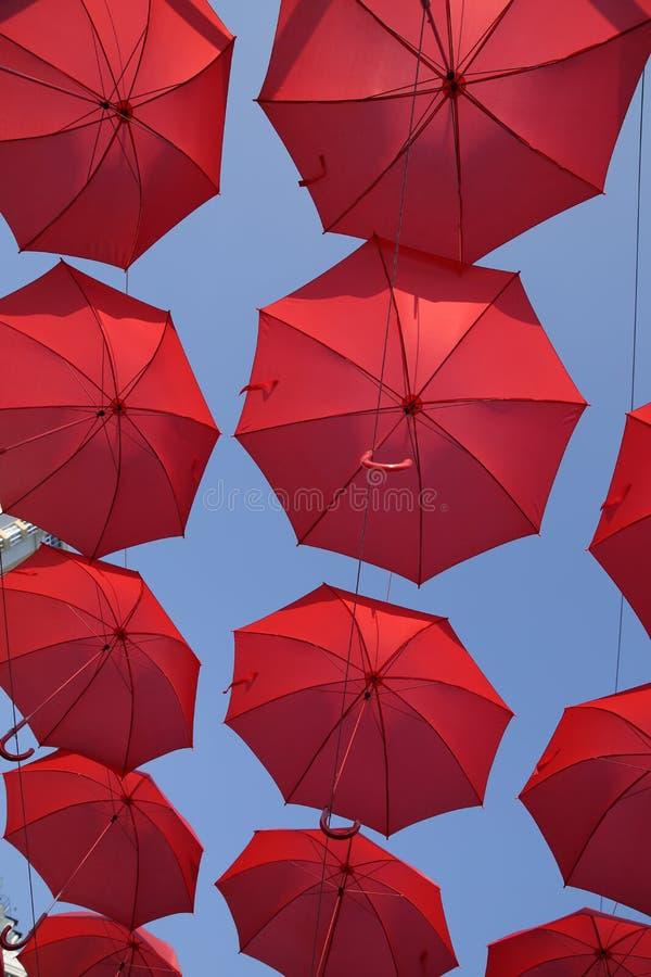 Viele roten Regenschirme gegen den blauen Himmel Ansicht von unterhalb Abstrakter Hintergrund mit roten Regenschirmen stockfotografie
