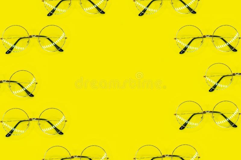 Viele runden Gläser, die als Rahmen auf gelbem Hintergrund liegen Spitzenstandpunkt, flache Lage lizenzfreies stockbild