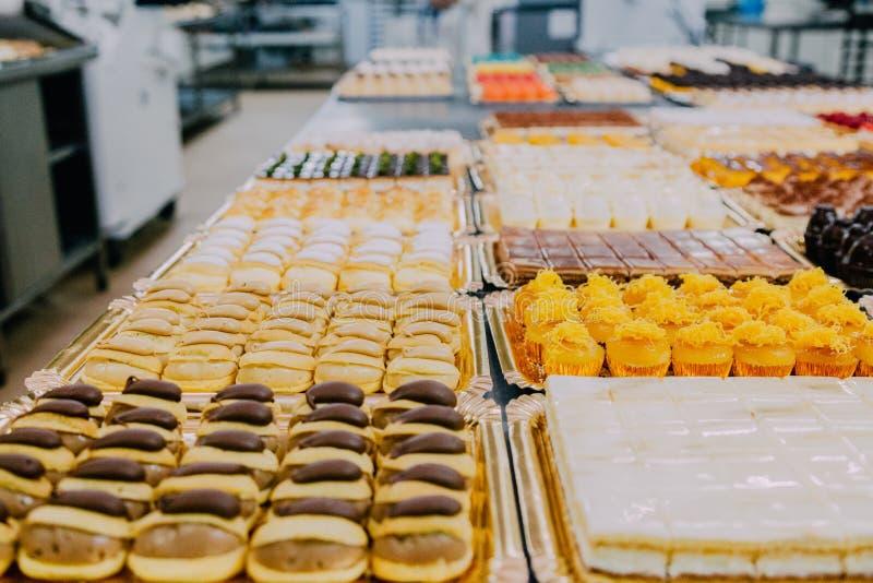 Viele süßen Teller vorbereitet auf die Metalltabelle einer Nahrungsmittelfabrik stockbild