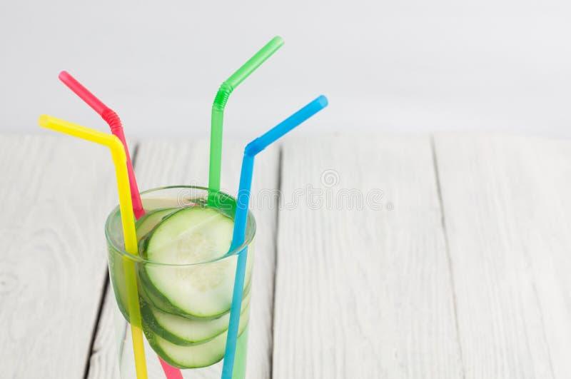 Viele Scheiben der grünen frischen Gurke im Glas mit Wasser und buntem Plastikröhrchen vier auf alten hölzernen Planken lizenzfreies stockfoto