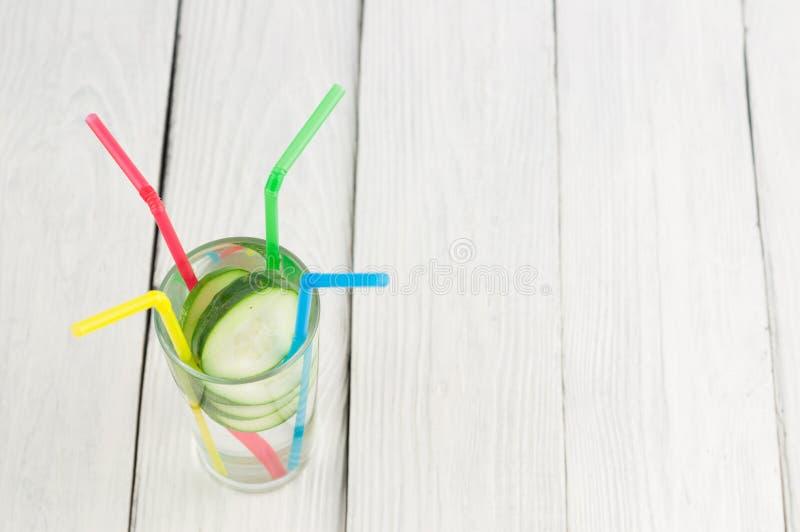 Viele Scheiben der grünen frischen Gurke im Glas mit Wasser und buntem Plastikröhrchen vier auf alten hölzernen Planken lizenzfreie stockbilder
