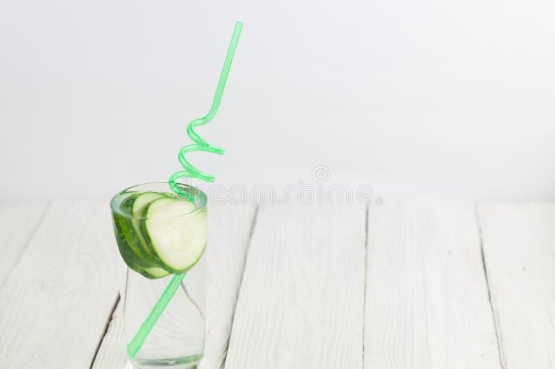 Viele Scheiben der grünen frischen Gurke im Glas mit Wasser und grünem gewundenem Plastikröhrchen auf alten hölzernen Planken lizenzfreie stockbilder