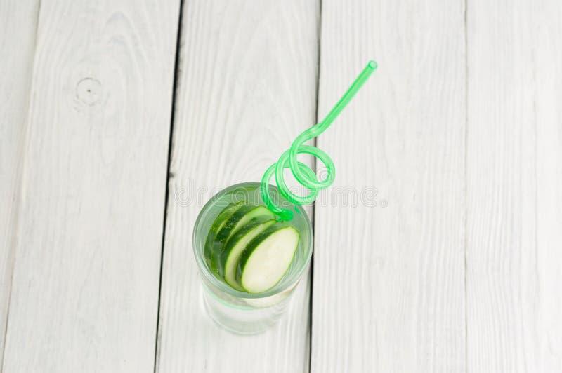 Viele Scheiben der grünen frischen Gurke im Glas mit Wasser und grünem gewundenem Plastikröhrchen auf alten hölzernen Planken stockbilder