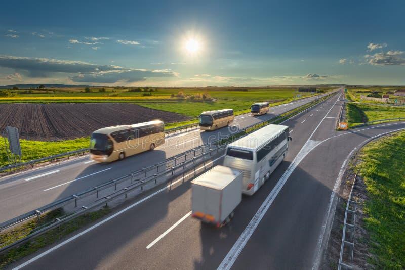 Viele schnellen Reisebusse auf der Autobahn bei Sonnenuntergang lizenzfreies stockfoto
