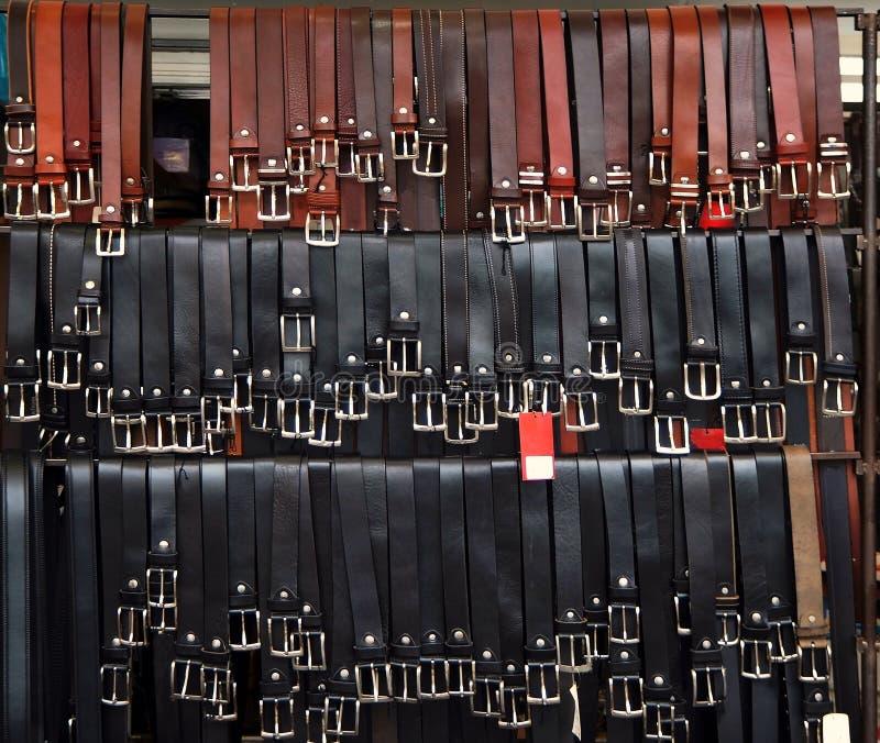 Viele schwarzen und braunen Ledergürtel, die an einem Bekleidungsgeschäft-Ausstellungsstand hängen lizenzfreies stockbild