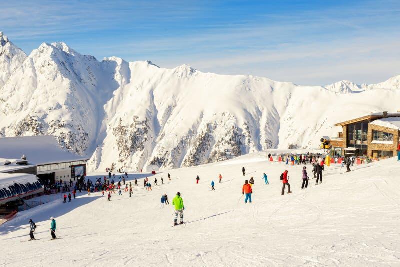 Viele Skifahrer und Snowboarder reiten auf dem Idalp Abfahrplato im österreichischen Alpin Ischgl Resort an sonniger Sonnentage b stockfotos