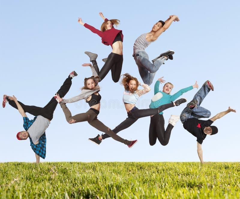 Viele springenden Leute auf dem Gras stockfotos