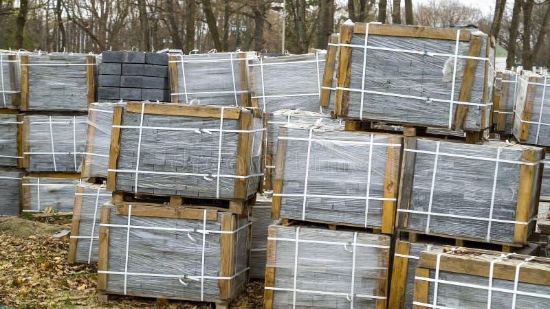 Viele Stapel Pflastersteine, die im Film eingewickelt werden, werden auf dem Boden draußen gespeichert stockbilder