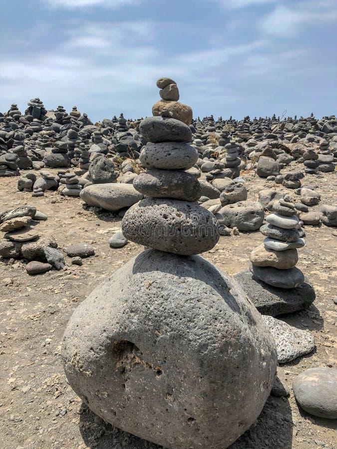 Viele Steinstapel auf dem Strand nahe Ozean in Teneriffa stockfoto