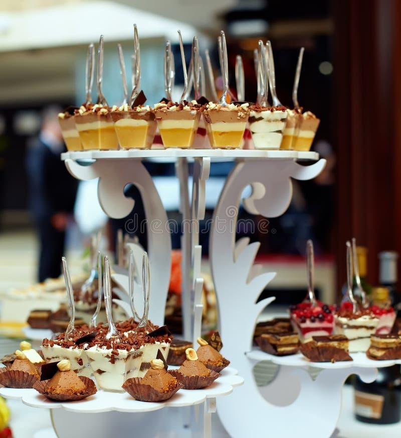 Viele Umhüllungen des süßen geschmackvollen Nachtischs auf Buffet lizenzfreie stockfotos