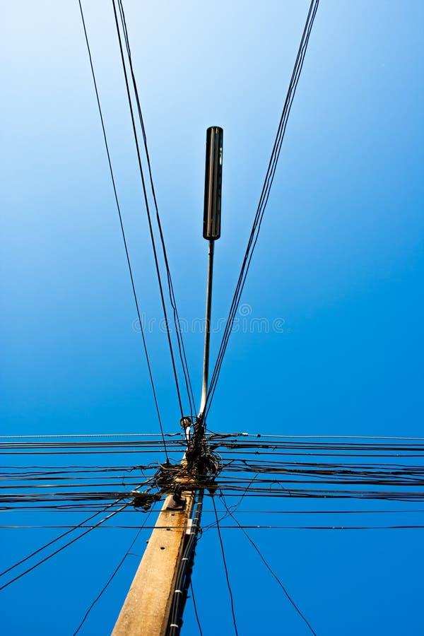 Viele verdrahten, elektrische Linien und Laternenpfahl auf dem Strombeitrag stockfotografie