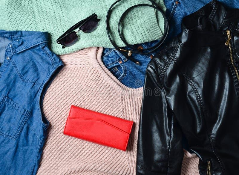 Viele verschiedenen Frauen u. x27; s-Kleidung und -Zubehör Strickjacke, Denimhemd, Jeans, Lederjacke, Geldbeutel, Gurt, Sonnenbri lizenzfreie stockfotografie