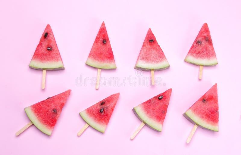 Viele verschiedenen hellen reifen Scheiben der Wassermelone auf einem Stock auf einem hellen rosa Hintergrund stockfoto