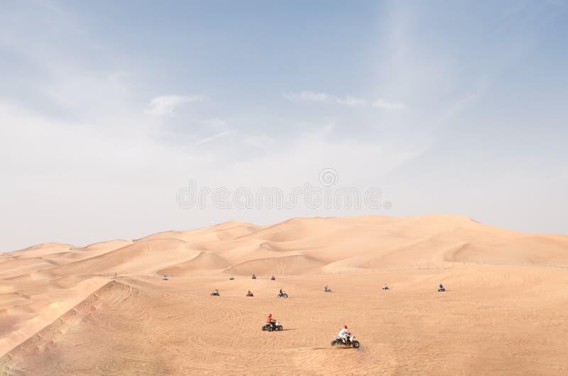 Viele viererverseilen die Reiter des Fahrrades ATV, die an der Station auf rote Wüstenhügel fahren lizenzfreie stockfotografie