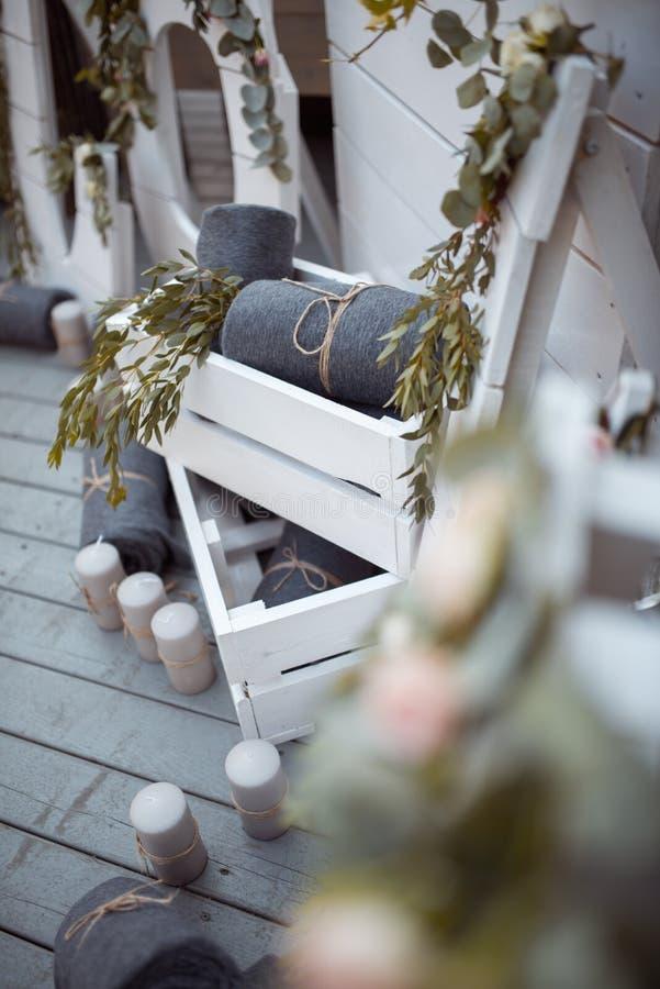 Viele Weiß gemalten hölzernen Käfigkästen, einige mit dekorativen Kerzen, rollten Decken und inländische Anlagen lizenzfreie stockfotos