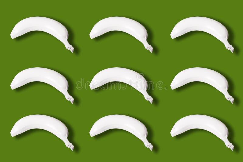 viele weißen farbigen Bananen lokalisiert auf grünem Hintergrund stockfoto