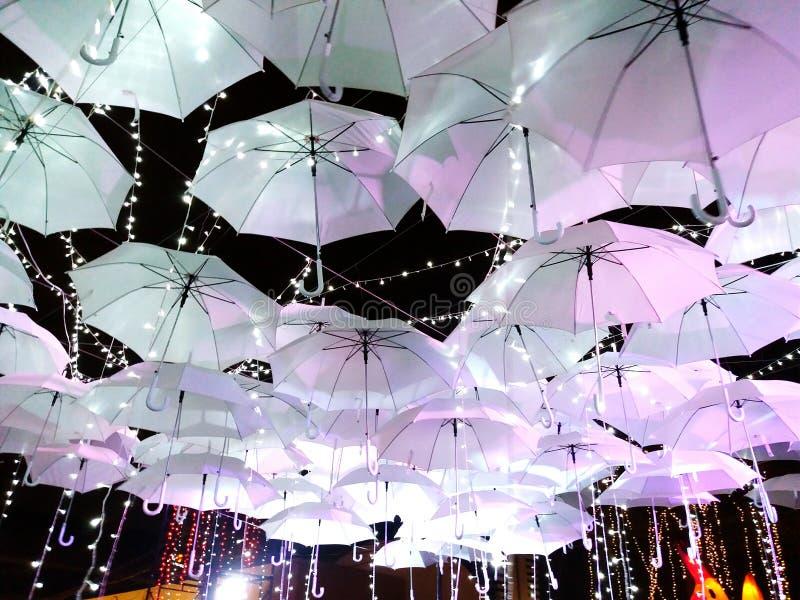 Viele weißen Regenschirme, die mit Licht auf Nachtstraße hängen lizenzfreie stockbilder