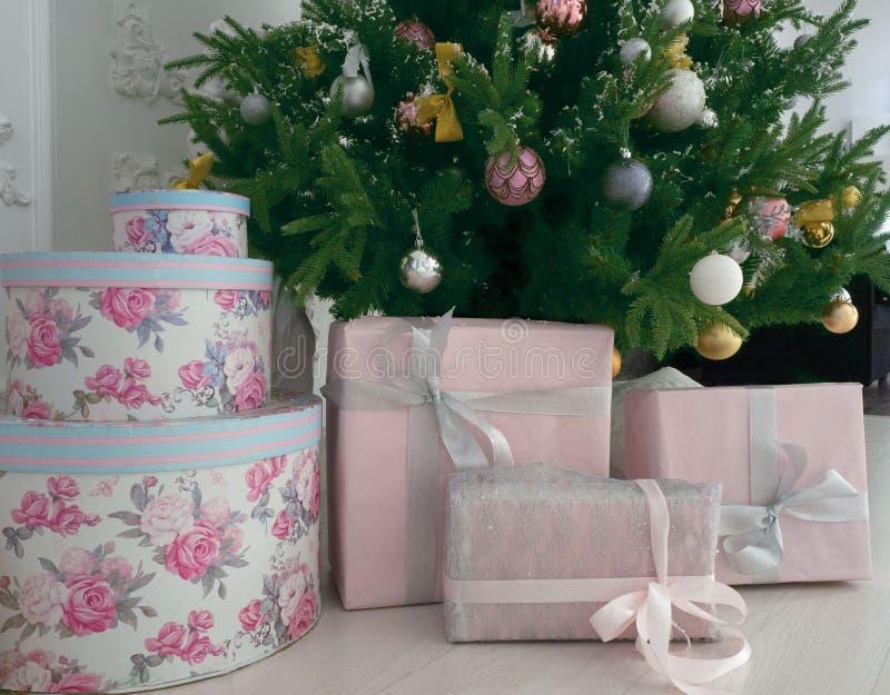 Viele Weihnachtsgeschenke auf dem Boden auf einem Weihnachtsbaumhintergrund stockfotografie