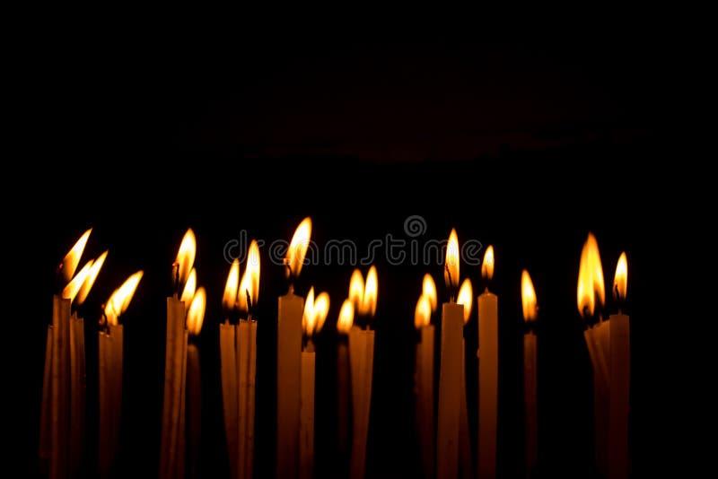 Viele Weihnachtskerzen, die nachts auf dem schwarzen Hintergrund brennen stockfoto