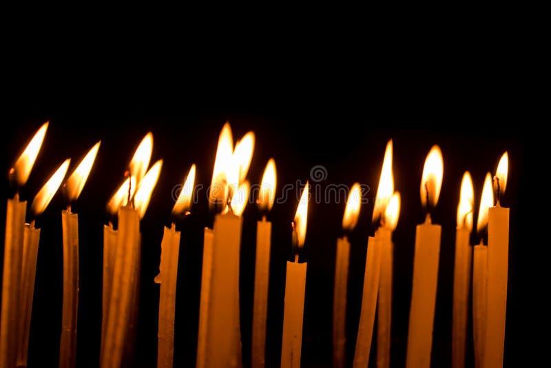 Viele Weihnachtskerzen, die nachts auf dem schwarzen Hintergrund brennen stockbild