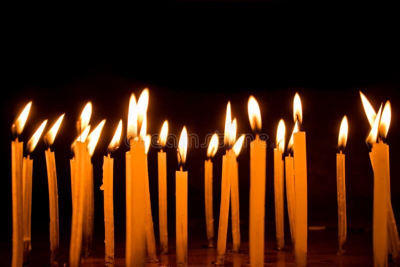 Viele Weihnachtskerzen, die nachts auf dem schwarzen Hintergrund brennen stockbilder