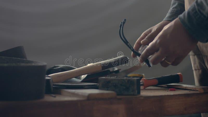 Viele Werkzeuge auf der Arbeitskrafttabelle und seiner Hand, die ein des Werkzeugs wählen stockfotos
