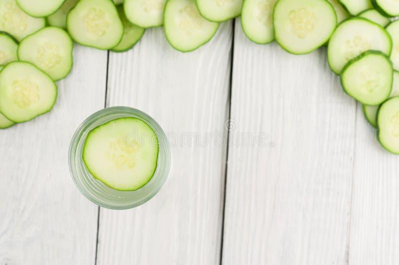 Viele zerstreuten frischen grünen Gurken der Scheiben und einzelne Scheibe im Glas mit Wasser auf alten hölzernen Planken lizenzfreie stockfotografie