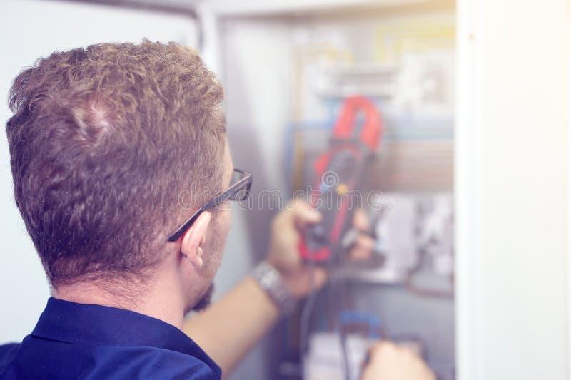 Vielfachmessgerät ist in den Händen des Elektrikers auf Hintergrund von electrica stockfotografie