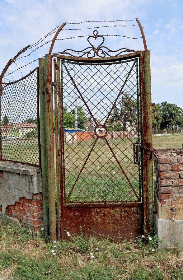 Vielle porte en métal rouillé à côté d'un mur en briques ruinées photo libre de droits