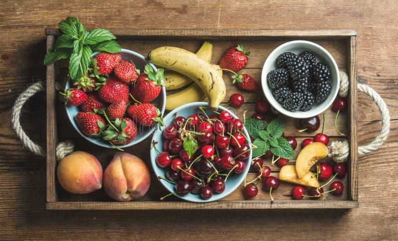 Vielzahl der frischen Frucht und der Beere des Sommers im rustikalen hölzernen Behälter lizenzfreie stockfotos