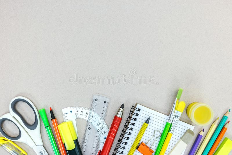 Vielzahl des Schulbedarfs mit Bleistiften, Notizbuch, Markierungen auf GR stockbild