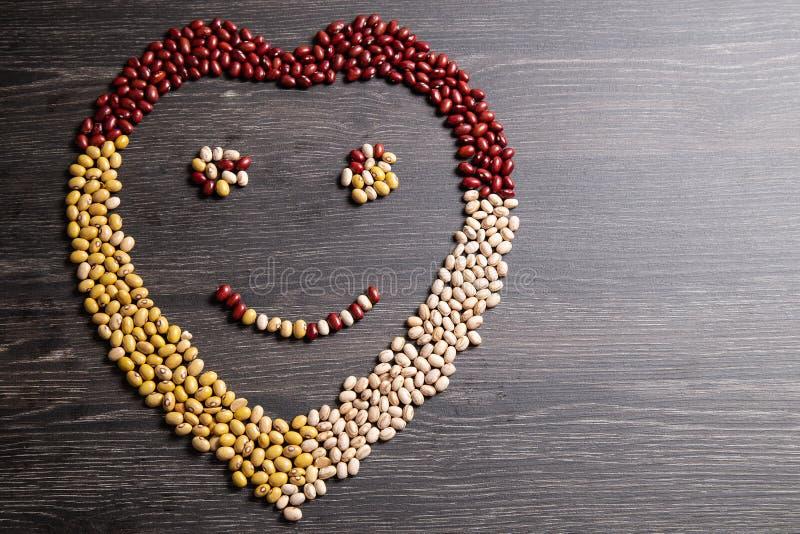 Vielzahl von Bohnen auf hölzernem Löffel auf hölzernem Hintergrund Mungobohnen, Erdnüsse, rote Bohnen und braune Bohnen stockfotografie