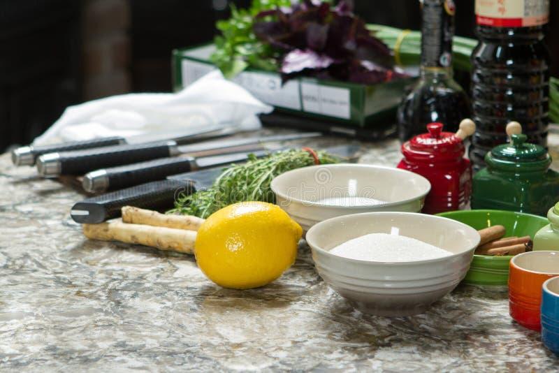 Vielzahl von Gewürzen, von Messern, von Kräutern und von Tellern auf Küchentisch stockfotografie