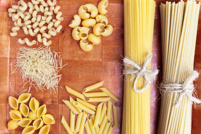 Vielzahl von trockenen rohen italienischen traditionellen Teigwaren auf hölzernem Schreibtisch stockfoto
