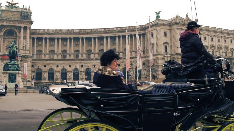 VIENA, ÁUSTRIA - DEZEMBRO, 24 transportes puxados por cavalos retros contra a biblioteca nacional austríaca em Heldenplatz popula fotos de stock royalty free