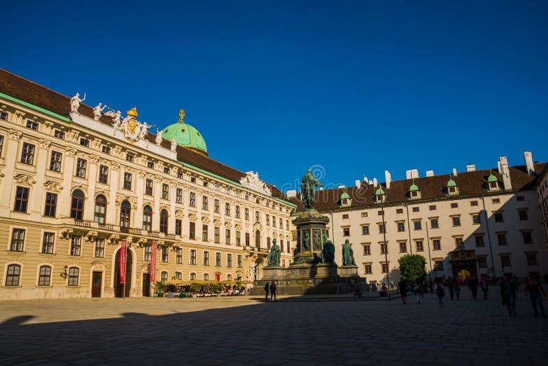 Viena, Áustria: Palácio de Hofburg e vista quadrada panorâmico, passeio dos povos e fiaker com os cavalos brancos em Viena, Áustr imagem de stock