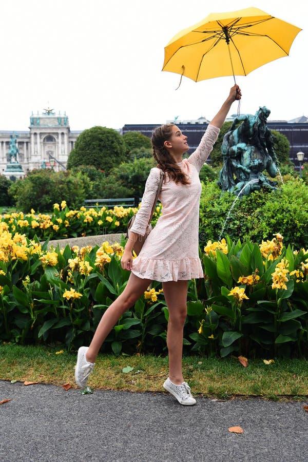 Viena, Áustria Uma menina com um guarda-chuva amarelo no fundo do Burg de Neue, um castelo novo do Hofburg P imagem de stock