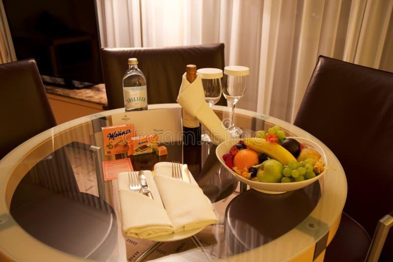 VIENA, AUSTRIA - 28 de abril de 2017: Tarde romántica con la botella de vino rojo, de dulces y de frutas en la habitación de lujo imagenes de archivo