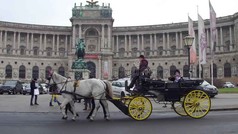 VIENA, AUSTRIA - DICIEMBRE, 24 carros traídos por caballo retros contra biblioteca nacional austríaca en Heldenplatz popular foto de archivo