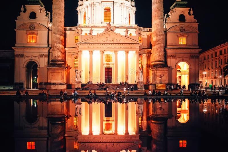 Viena, Austria Karlskirche en la noche con la reflexión del agua y gente que está sin hacer nada imagen de archivo