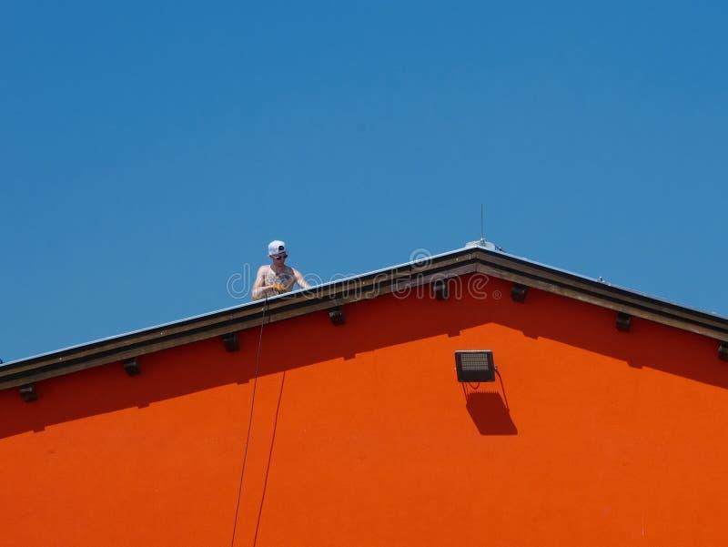 Viena - 5 de junio de 2019: hombre descamisado que trabaja en un tejado de un compuesto industrial imagenes de archivo