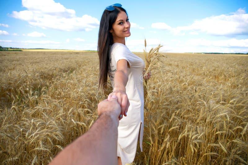 Viene conmigo, la muchacha hermosa joven lleva a cabo la mano de un hombre en un campo de trigo fotos de archivo libres de regalías