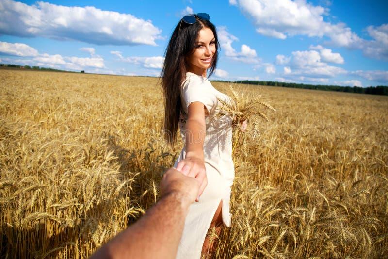 Viene conmigo, la muchacha hermosa joven lleva a cabo la mano de un hombre en un campo de trigo imagen de archivo