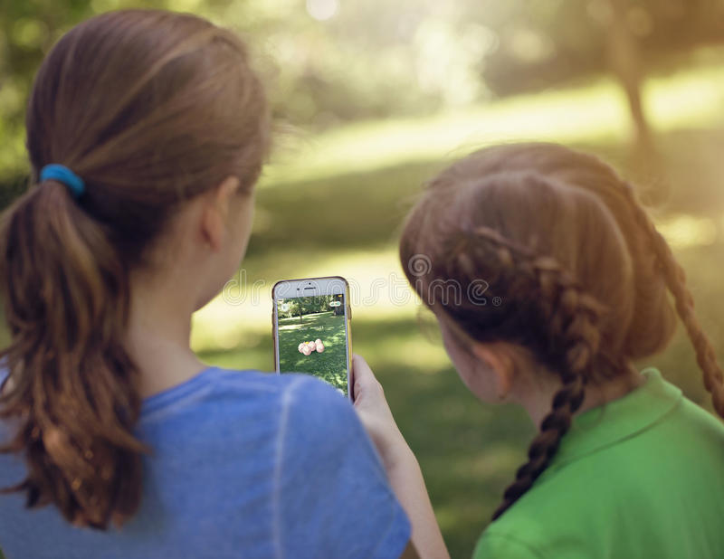 Vienna, AUSTRIA - August 1, 2016: Little girls playing a Pokemon royalty free stock photo