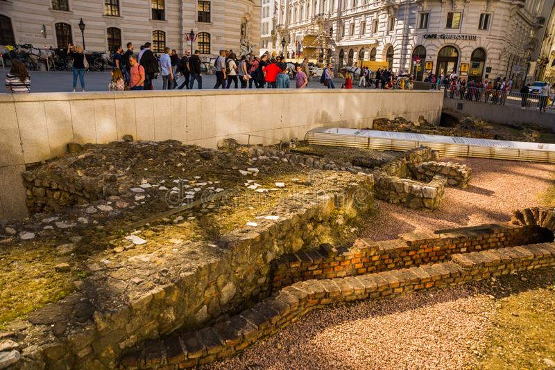 VIENNA, AUSTRIA: Cityscape views of one of Europe`s town- Vienna. Roman city ruins on a foregrond and peoples on streets royalty free stock image