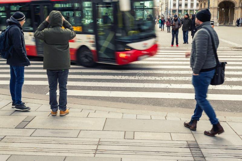 Vienna, Austria - 15 gennaio 2019: Pedoni dei turisti al bus aspettante di attraversamento che passa strada Scena di stile di vit fotografie stock libere da diritti
