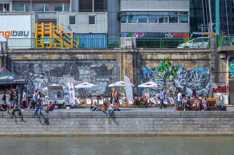 VIENNA, AUSTRIA - MAY 25: Many people are relaxing with alcohol drinks on a day off in a beautiful summer weather on the banks of royalty free stock image
