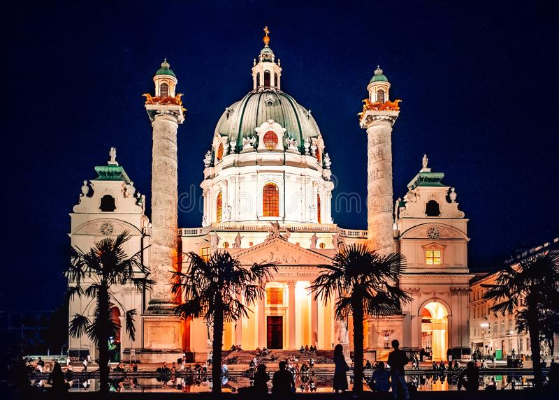 Vienna, Austria. Peoples silhouette at  Karlskirche Dome by night. Beautiful St Charles Church Karlskirche at night with people silhouettes sitting and standing royalty free stock image