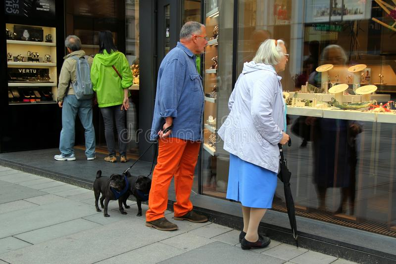 Couple of two elderly people with two dogs looking on a shop window of jewelry shop. stock photo